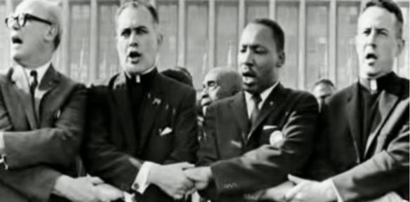 """Former otre Dame President Father Ted Hesburgh with Martin Luther King, Jr. at a civil rights rally in 1964."""